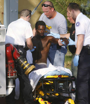 Photo - William Boyd Sturdivant II is helped onto a stretcher after coming down from the Clear Channel Communications building tower in Tulsa, Okla., Tuesday, Aug. 16, 2011, six days after he scaled the tower. (AP Photo/The Tulsa World, James Gibbard)