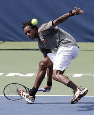Photo - Gael Monfils, of France, returns a shot against Fernando Verdasco, of Spain, during a quarterfinal match in the Winston-Salem Open tennis tournament in Winston-Salem, N.C., Thursday, Aug. 22, 2013. (AP Photo/Chuck Burton)