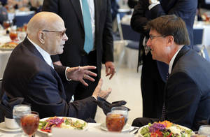 Photo - Charlotte Motor Speedway chairman Bruton Smith, left, talks with North Carolina Gov. Pat McCrory, right, before a news conference at the NASCAR Sprint Cup auto racing Media Tour in Charlotte, N.C., Monday, Jan. 27, 2014. (AP Photo/Chuck Burton)