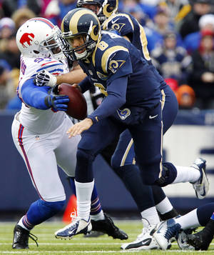Photo - Buffalo Bills defensive end Mario Williams, left, forces a fumble on St. Louis Rams quarterback Sam Bradford during the first half of an NFL football game, Sunday, Dec. 9, 2012, in Orchard Park, N.Y. Bradford recovered the ball on the play. (AP Photo/Bill Wippert)