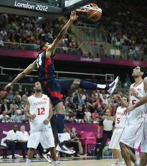 Photo -   USA's Anthony Davis slams a dunk between Tunisian players during a men's basketball game at the 2012 Summer Olympics, Tuesday, July 31, 2012, in London. (AP Photo/Charles Krupa)