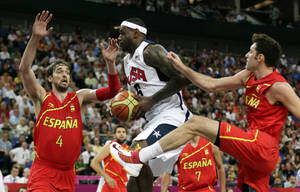 Photo -   United States' LeBron James drives between Spain's Pau Gasol and Rudy Fernandez during the men's gold medal basketball game at the 2012 Summer Olympics, Sunday, Aug. 12, 2012, in London. (AP Photo/Charles Krupa)