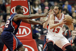 Photo - Chicago Bulls center Joakim Noah (13) drives against Atlanta Hawks forward Elton Brand, left, and Kyle Korver during the first half of an NBA basketball game in Chicago on Saturday, Jan. 4, 2014. (AP Photo/Nam Y. Huh)