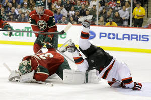 Photo - New Jersey Devils right wing Stephen Gionta, right, sails over Minnesota Wild goalie Josh Harding, center, as Harding covers the puck after stopping a shot by Gionta during the second period of an NHL hockey game in St. Paul, Minn., Sunday, Nov. 3, 2013. (AP Photo/Ann Heisenfelt)