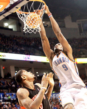 Photo - Thunder forward Serge Ibaka slams in a basket over Toronto's Amir Johnson during Oklahoma City's 119-99 win Sunday at the Ford Center.  PHOTO BY JOHN CLANTON, THE OKLAHOMAN