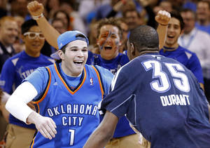 Photo - Justin Dougherty is greeted by Oklahoma City's Kevin Durant (35) after he made a 20,000 dollar half-court shot during the NBA basketball game between the Oklahoma City Thunder and the Portland Trail Blazers at the Chesapeake Energy Arena in Oklahoma City, Sunday, March, 24, 2013. (AP Photo/The Oklahoman, Sarah Phipps)