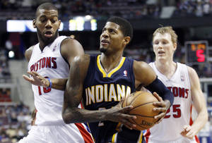 photo - Indiana Pacers forward Paul George, center, goes to the basket against Detroit Pistons center Greg Monroe, left, and forward Kyle Singler during the second half of an NBA basketball game Saturday, Feb. 23, 2013, in Auburn Hills, Mich. George scored 12 points, pulled down 12 rebounds and dished out eight assists in the Pacers' 90-72 win. (AP Photo/Duane Burleson)