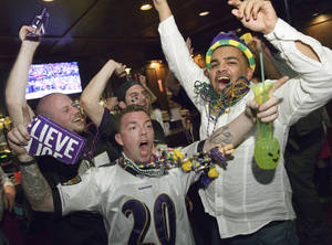 Photo - Lee Fuller, of Baltimore, center, and others celebrate the Baltimore Ravens winning the Super Bowl at the Famous Door Bar as fans of the Ravens and San Francisco 49ers NFL football teams pack the French Quarter on Bourbon Street for Super Bowl XLVII in New Orleans, Sunday, Feb. 3, 2013. (AP Photo/Matthew Hinton)