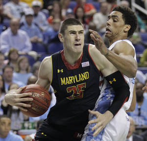 Photo - Maryland's Alex Len, left, drives past North Carolina's James Michael McAdoo during the first half of an NCAA college basketball game in the semifinals of the Atlantic Coast Conference tournament in Greensboro, N.C., Saturday, March 16, 2013. (AP Photo/Bob Leverone)