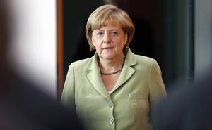 Photo - German Chancellor Angela Merkel arrives for the weekly cabinet meeting at the chancellery in Berlin, Germany, Wednesday, Aug. 21, 2013. (AP Photo/Michael Sohn)