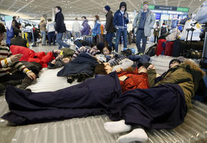 photo - Travelers take a rest on a floor at departure lobby at Narita airport in Narita, near Tokyo Tuesday, Jan. 15, 2013 as they stayed overnight due to heavy snow. This winter's first snow in Tokyo on Monday severely disrupted train services, canceled flights and stranded tourists. (AP Photo/Kyodo News) JAPAN OUT, MANDATORY CREDIT, NO LICENSING IN CHINA, HONG KONG, JAPAN, SOUTH KOREA AND FRANCE