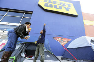 Photo - Denise Smith-Lad, left, asks her grandson Jordan Smith, 6, what he would like to eat Monday as they camp in front of a Best Buy store in Cockrell Hill, Texas. Smith and her family have come early to line up for The shopping deals available the day after Thanksgiving. AP Photo