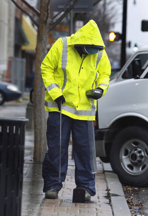 Photo - City of Norman employee Michael Childress reads water meters on Main St as a winter storm moves into the area on Thursday, Jan. 28, 2010, in Norman, Okla.  Photo by Steve Sisney, The Oklahoman