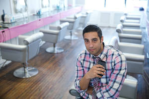 Photo - In this May 19, 2014 photo, Avi Shenkar, owner of Blo/Out Blow Dry Bars, poses for a photograph with his iPhone, in Philadelphia. Smartphones have become vital for on-the-go entrepreneurs such as Shenkar who runs his four hair salons from the palm of his hand. (AP Photo/Matt Rourke)
