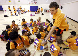 Photo - Counselor John Kastner says he tries to share a positive attitude with day campers at the Edmond branch of the YMCA. Photos by David McDaniel, The Oklahoman