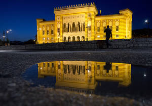Photo - In this Tuesday, April 22, 2014, the City Hall is reflected in a puddle in Sarajevo, Bosnia-Herzegovina. The city will host a number events around the Centenary of World War I, including a conference of historians and a concert. (AP Photo/Amel Emric)