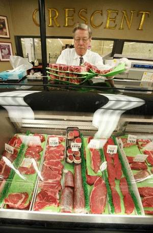 Photo - Leo Gulikers puts out fresh cut rib eyes at Crescent Market in Nichols Hills , Monday, October 3, 2011. Gulikers has worked for Crescent Market for 27 years. Photo by Steve Gooch  ORG XMIT: KOD