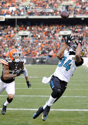 Photo - Jacksonville Jaguars wide receiver Cecil Shorts (84) catches a 20-yard touchdown pass against Cleveland Browns cornerback Joe Haden (23) in the fourth quarter of an NFL football game on Sunday, Dec. 1, 2013 in Cleveland. The score gave the Jaguars a 32-28 win over the Browns. (AP Photo/David Richard)