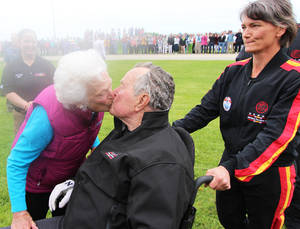 Photo - In this photo provided by the All Veteran Parachute Team, Barbara Bush kisses former President George H.W. Bush after his landing of a parachute jump on his 90th birthday in Kennebunkport, Maine, Thursday, June 12, 2014. (AP Photo/All Veteran Parachute Team, Kenneth Wasley)