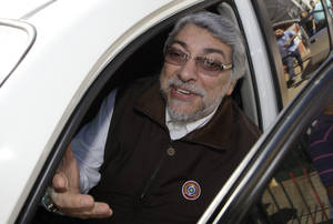 Photo -   Paraguay's former President Fernando Lugo talks to journalists from a car at the Pais Solidario Party headquarters in Asuncion, Paraguay, Wednesday, June 27, 2012. Lugo has surprised Paraguayans with conflicting announcements since the Senate voted to remove him from office last week. At first, he said he would comply and leave office. Then, he said he would fight the decision and make his case to the region's leaders. (AP Photo/Jorge Saenz)