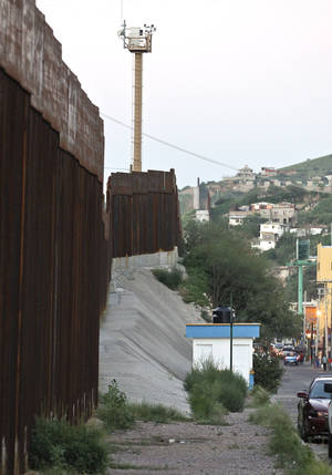 photo -   This Aug. 9, 2012, photo shows the border fence with security camera towers in the distance in Nogales, Mexico. The location is near the site where a U.S. Border Patrol agent being pelted with rocks opened fire toward Mexico, killing a 16-year-old boy. The shooting has prompted renewed outcry over the Border Patrol's use-of-force policies and angered human rights activists and Mexican officials who believe the incident has become part of a disturbing trend along the border _ gunning down rock-throwers rather than using non-lethal weapons. (AP Photo/Ross D. Franklin)
