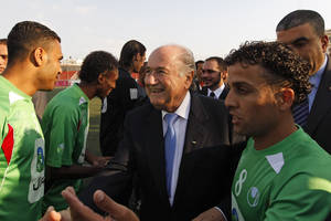 Photo - FILE -  In this May 15, 2011 file photo, FIFA president Joseph S. Blatter, center, greets members of the Palestinian refugee camp team from Amari before their friendly match against the Senegalese club team Dakar, in the West Bank town of Aram, near Ramallah. Israel's sports minister has written to FIFA President Sepp Blatter, defending her country's travel restrictions on some Palestinian soccer players. The Palestine Football Association has called on FIFA to suspend Israel unless it lifts travel restrictions on his players. (AP Photo/Tara Todras-Whitehill, file)