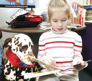 Photo - Paige Fowler, 6, reads to D'Leo, a Dalmatian therapy dog, at the Nicoma Park Library. D'Leo visits the library Thursday as part of the Children Reading to Dogs program. PHOTO BY STEVE GOOCH, THE OKLAHOMAN