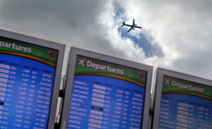 Photo - A plane takes off over a departure board at Hartsfield-Jackson Airport, Wednesday, Nov. 27, 2013, in Atlanta. Rain and snow on the East Coast did not ripple out into the widespread meltdown that had been feared. (AP Photo/David Goldman)