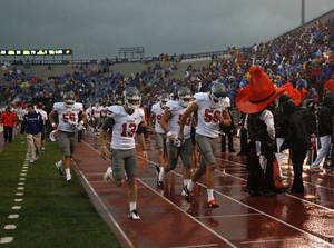 Photo - OSU leaves the field during a rain delay at the college football game between Oklahoma State University (OSU) and the University of Kansas (KU) at Memorial Stadium in Lawrence, Kan., Saturday, Oct. 13, 2012. Photo by Sarah Phipps, The Oklahoman