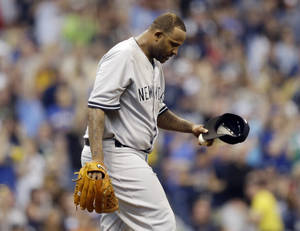 Photo - New York Yankees starting pitcher CC Sabathia looks down after giving up a home run to Milwaukee Brewers' Aramis Ramirez in the third inning of a baseball game Saturday, May 10, 2014, in Milwaukee. (AP Photo/Jeffrey Phelps)
