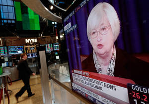 Photo - A television screen on the floor of the New York Stock Exchange shows Federal Reserve Chair Janet Yellen's first news conference, in Washington D.C., Wednesday, March 19, 2014.  The Federal Reserve is seeking to clarify when it might start to raise short-term interest rates from record lows. The Fed also says it will cut its monthly long-term bond purchases by another $10 billion to $55 billion because it thinks the economy is strong enough to support further improvements in the job market. (AP Photo/Richard Drew)