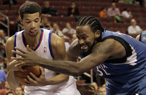 Photo - Minnesota Timberwolves' Ronny Turiaf, right, and Philadelphia 76ers' Michael Carter-Williams fight for the ball in the first half of a preseason NBA basketball game, Wednesday, Oct. 23, 2013, in Philadelphia. (AP Photo/Laurence Kesterson)