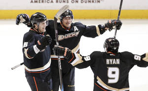 Photo - Anaheim Ducks right wing Teemu Selanne, middle, celebrates his goal with Ben Lovejoy, left, and Bobby Ryan against the Detroit Red Wings during the third period in Game 1 of their first-round NHL hockey Stanley Cup playoff series in Anaheim, Calif., Tuesday, April 30, 2013. (AP Photo/Chris Carlson)