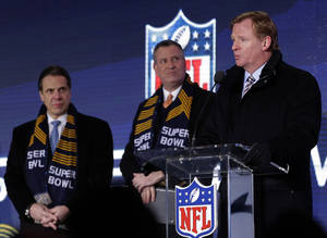 Photo - NFL comissioner Roger Goodell, right, speaks while New York City Mayor Bill de Blasio, center, and New York Gov. Andrew Cuomo, left, look on during a ceremony unveiling the Roman numerals for Super Bowl XLVIII on Super Bowl Boulevard Wednesday, Jan. 29, 2014, in New York. The Seattle Seahawks are scheduled to play the Denver Broncos in the NFL Super Bowl XLVIII football game on Sunday, Feb. 2, in East Rutherford, N.J.  (AP Photo/Charlie Riedel)