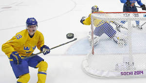Photo - Sweden forward Nicklas Backstrom watches a shot that got past Sweden goaltender Henrik Lundqvist during a men's semifinal ice hockey game against Finland at the 2014 Winter Olympics, Friday, Feb. 21, 2014, in Sochi, Russia. (AP Photo/David J. Phillip)