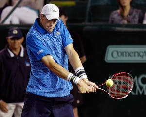Photo - John Isner, of the United States, hits a return to Dustin Brown, of Germany, at the U.S. Men's Clay Court Championship tennis tournament, Wednesday, April 9, 2014, in Houston. (AP Photo/Houston Chronicle, Bob Levey) MANDATORY CREDIT