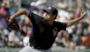Photo - Colorado Rockies starting pitcher Jorge De La Rosa throws to the San Francisco Giants during the second inning of an exhibition baseball game in Scottsdale, Ariz., Wednesday, March 26, 2014. (AP Photo/Chris Carlson)