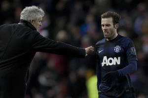 Photo - Manchester United's Juan Mata, right, walks past the opposing team's manager Mark Hughes after his team's 2-1 loss at Stoke in their English Premier League soccer match at the Britannia Stadium, Stoke, England, Saturday Feb. 1, 2014. (AP Photo/Jon Super)