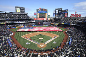 Photo - A giant American flag is unfurled before a baseball game between the New York Mets and Washington Nationals on opening day at Citi Field, Monday, March 31, 2014, in New York. (AP Photo/John Minchillo)