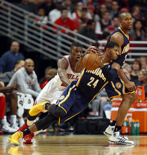 Photo - Indiana Pacers forward Paul George (24) tries to control the ball in front of Chicago Bulls guard Jimmy Butler, left, during the second quarter of an NBA basketball game in Chicago, Saturday, Nov. 16, 2013. (AP Photo/Kamil Krzaczynski)