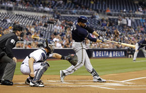 Photo - Milwaukee Brewers' Ryan Braun, right, hits a two-run home run with San Diego Padres catcher Nick Hundley, center, looking on in front of home plate umpire Clint Fagan in the first inning of a baseball game, Monday, April 22, 2013, in San Diego. (AP Photo/Alex Gallardo)