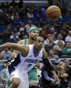 Photo - Orlando Magic's Arron Afflalo (4) and Boston Celtics' Jerryd Bayless go after a loose ball during the first half of an NBA basketball game in Orlando, Fla., Sunday, Jan. 19, 2014. (AP Photo/John Raoux)