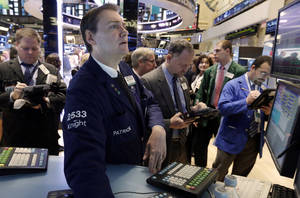Photo - Specialist Patrick King, second left, works on the floor of the New York Stock Exchange Tuesday, Jan. 8, 2013. U.S. stocks opened mostly lower Tuesday as traders awaited the start of U.S. corporate earnings season. (AP Photo/Richard Drew)