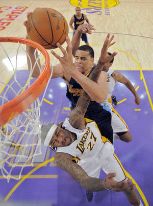 Photo -   Denver Nuggets center JaVale McGee, top, grabs a rebound away from Los Angeles Lakers center Jordan Hill during the second half of an NBA first-round playoff basketball game, Sunday, April 29, 2012, in Los Angeles. The Lakers won 103-88. (AP Photo/Mark J. Terrill)