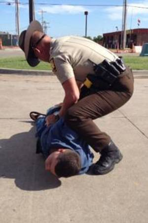 Photo -  A Canadian County sheriff's deputy handcuffs Dustin Crump, 27, of Marlow, who was accused of trying to meet a 15-year-old girl Friday afternoon. Photo provided  <strong>   -   </strong>