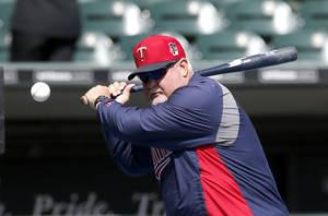 Photo - Minnesota Twins manager Ron Gardenhire hits infield practice before an opening day baseball game against the Chicago White Sox Monday, March 31, 2014, in Chicago. (AP Photo/Charles Rex Arbogast)