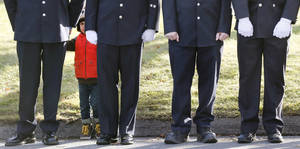 photo - A child peers through firefighters standing as the procession heads to the cemetery outside the funeral for school shooting victim Daniel Gerard Barden at St. Rose of Lima Catholic Church in Newtown, Conn., Wednesday, Dec. 19, 2012. According to firefighters, Daniel wanted to be a firefighter when he grew up and they honored him at the service. Barden, 7, was killed when Adam Lanza walked into Sandy Hook Elementary School in Newtown, Conn., Dec. 14, and opened fire, killing 26 people, including 20 children, before killing himself. (AP Photo/Charles Krupa)