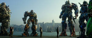 """Photo - This photo released by Paramount Pictures shows, from left, Hound, Bingbing Li as Su Yueming, Stanley Tucci as Joshua Joyce, Bumblebee, Jack Reynor as Shane Dyson, Nicola Peltz as Tessa Yeager, Mark Wahlberg as Cade Yeager, Optimus Prime, Drift, and Crosshairs, in a scene from the film, """"Transformers: Age of Extinction,"""" from Paramount Pictures. (AP Photo/Paramount Pictures, ILM)"""