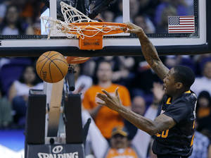 Photo - Phoenix Suns' Archie Goodwin dunks against the Orlando Magic during the first half of an NBA basketball game, Wednesday, March 19, 2014, in Phoenix. (AP Photo/Matt York)