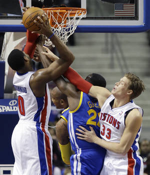 Photo - Detroit Pistons center Andre Drummond (0) recovers a rebound as teammate forward Jonas Jerebko (33) of Sweden and Golden State Warriors forward Draymond Green (23) reach in during the first half of an NBA basketball game in Auburn Hills, Mich., Monday, Feb. 24, 2014. (AP Photo/Carlos Osorio)